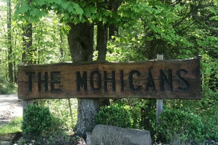 wood sign that says The Mohicans in front of a tree surrounded by greenery
