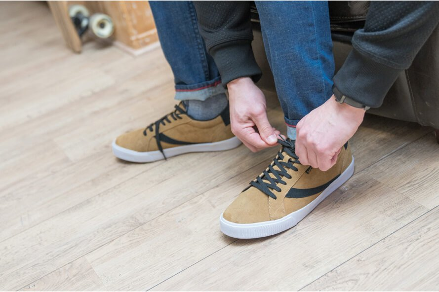 person ties light brown shoes
