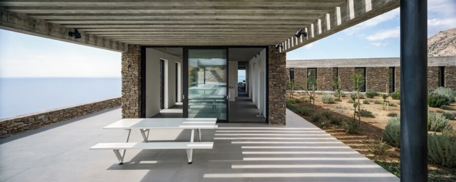 view of the homes outdoor terrace with a white table underneath it beside glass sliding doors
