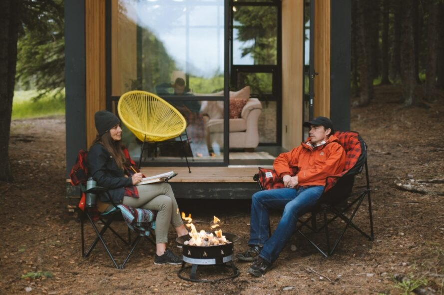 two people sitting outside a tiny cabin