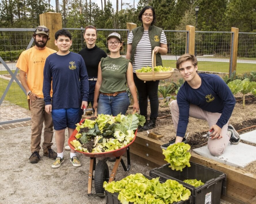 group of students proudly showing harvested produce