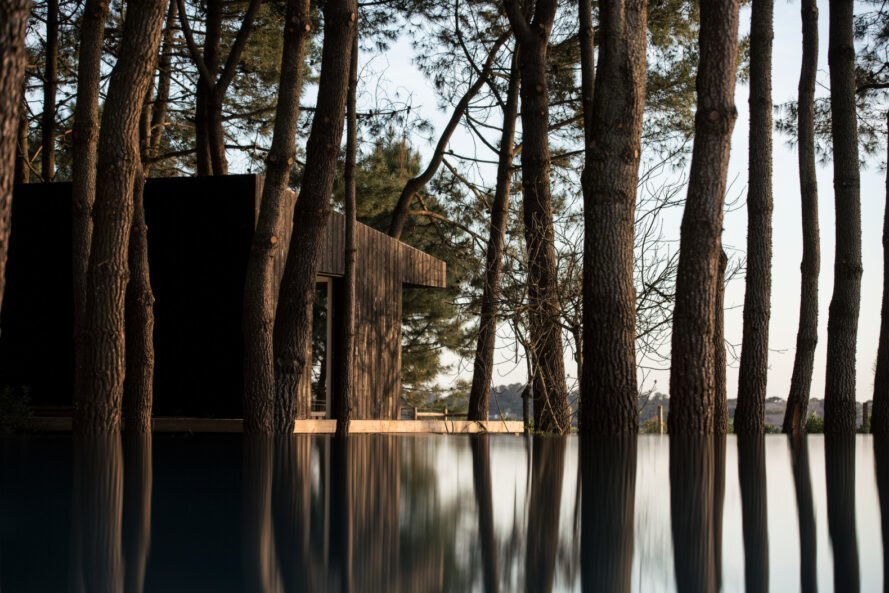black cabin overlooking water