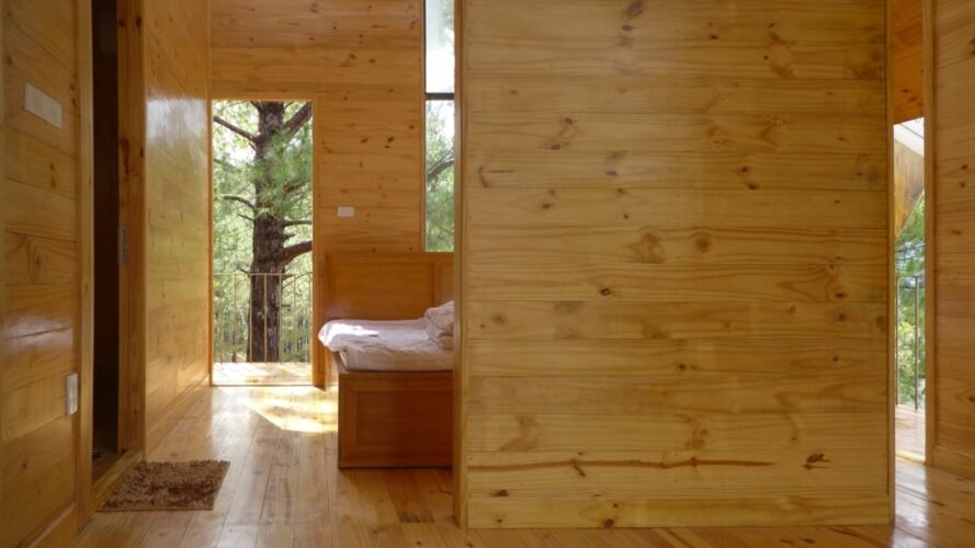 wood-lined interior with small plush bed