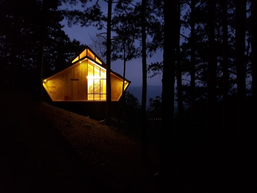 wood cabin lit up at night