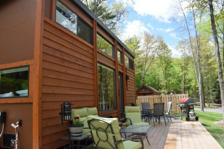 wooden tiny home with seating on large deck