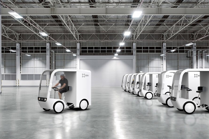 small white electric cargo quadricycle at a warehouse