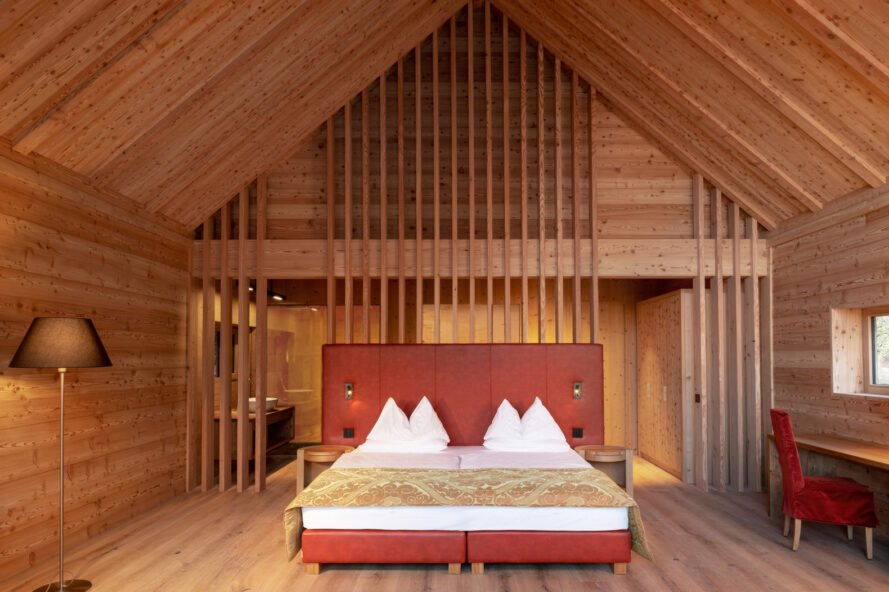 wood-lined bedroom with huge red bed
