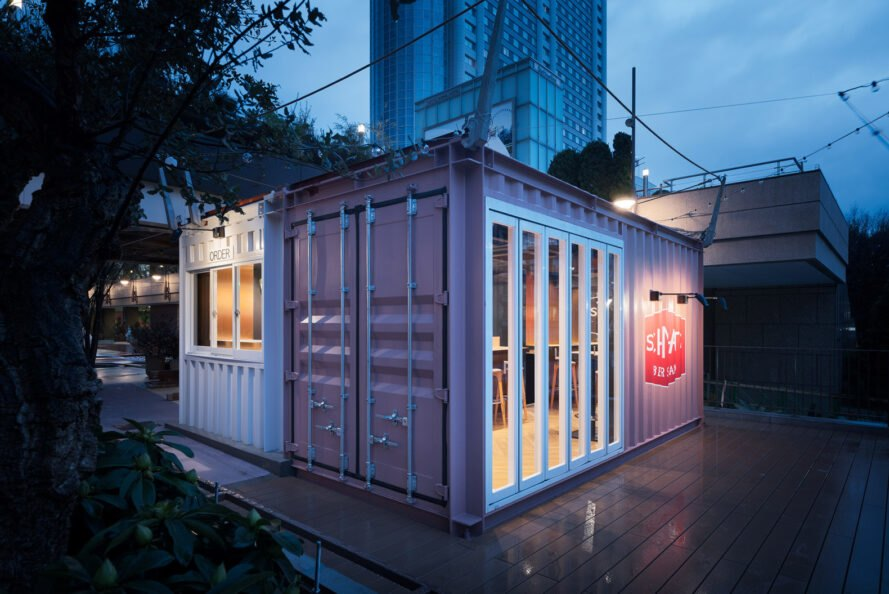 small gray shipping container lit up at night