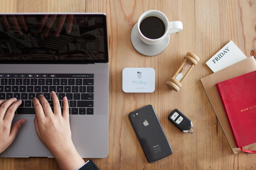 small white box of cutlery beside coffee mug and laptop
