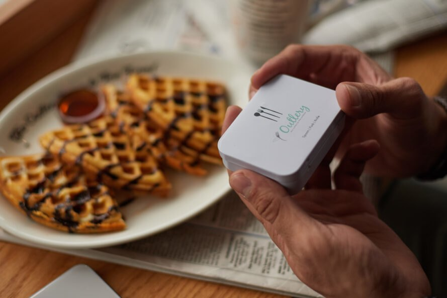 person opening small white box with cutlery inside