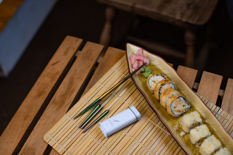 one chopstick and one disassembled chopstick beside plate of sushi