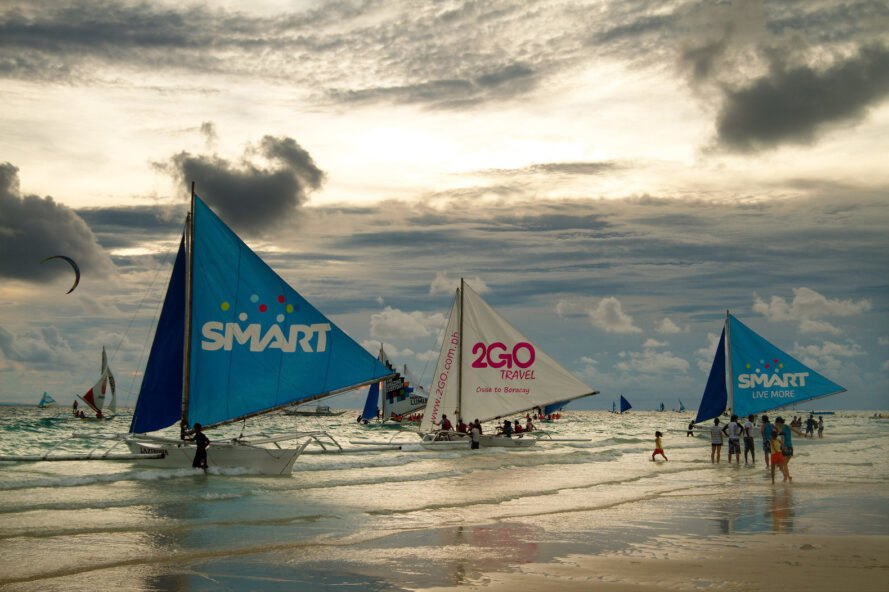 Sailboats and tourists at the shores of Boracay