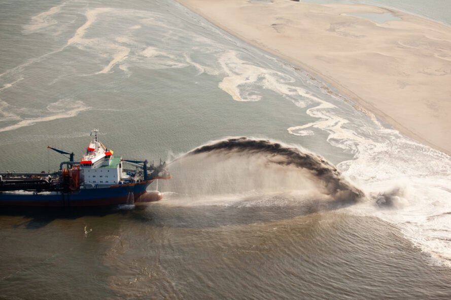 boat dredges sand along the coast