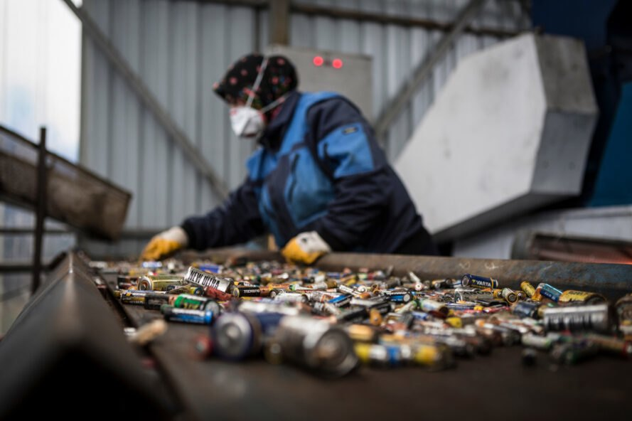 woman recycling batteries