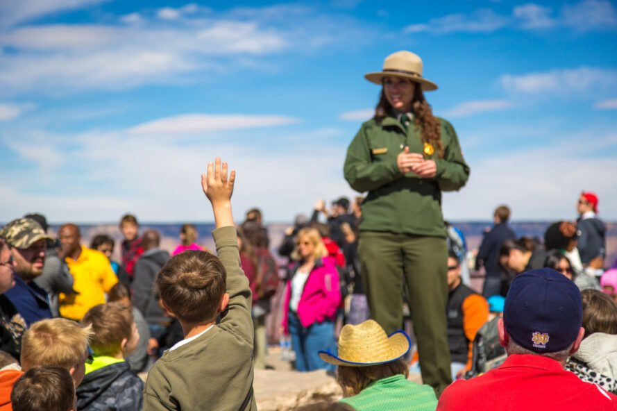 park ranger in green uniform provides numerous tourists with information
