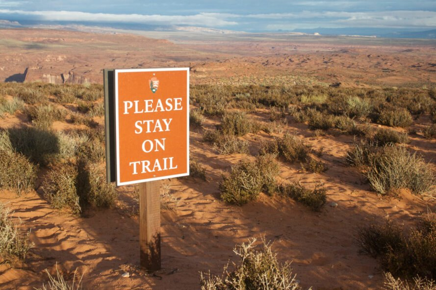 a sign at Horseshoe Bend says please stay on trail with large open land