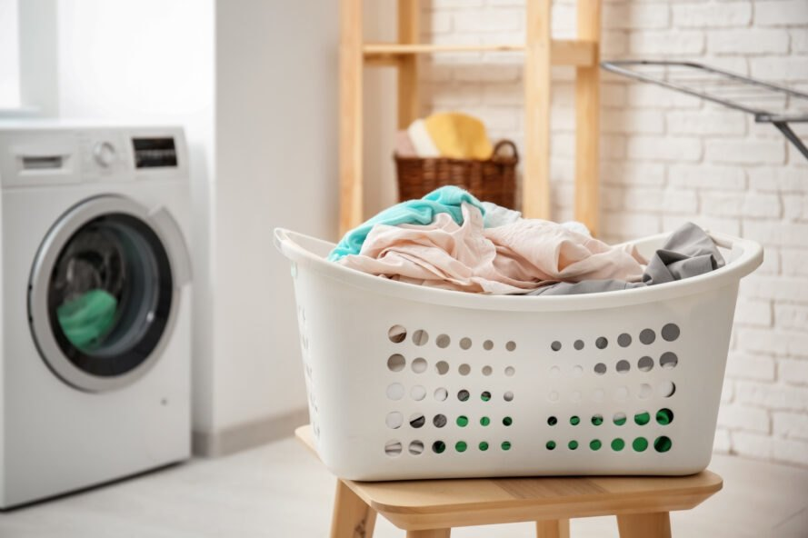 white plastic laundry basket filled with clothes placed on wooden stool in front of washing machine