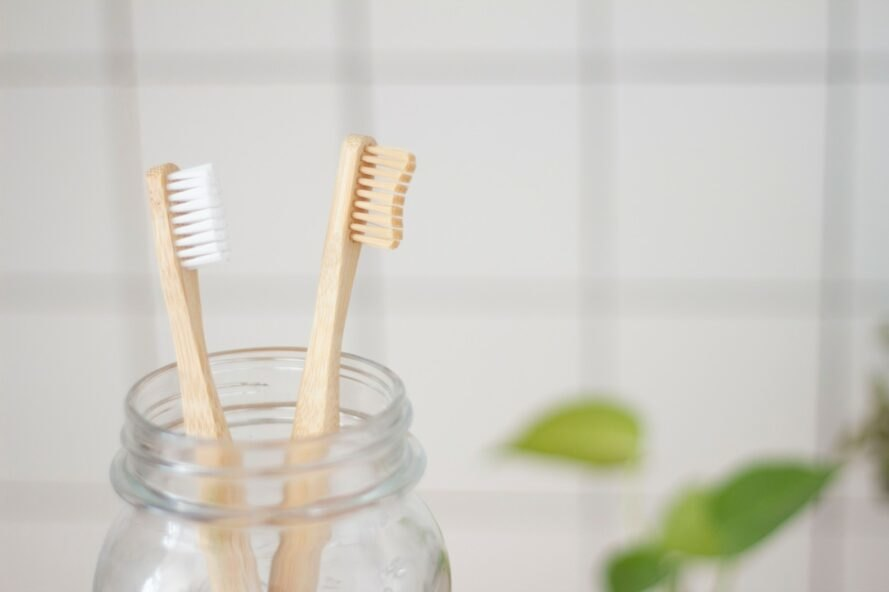 two bamboo toothbrushes inside a glass mason jar
