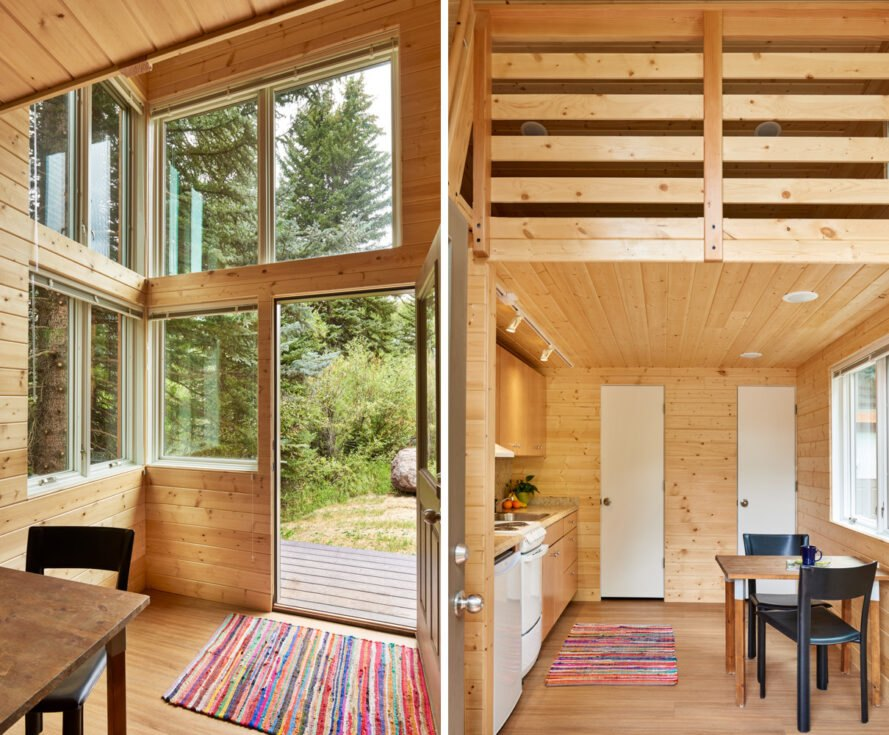 wood-lined interior of tiny homes with small kitchen and several windows