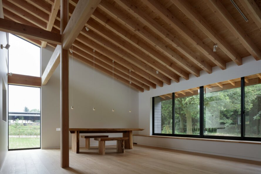minimalist interior space with exposed beams on pitched roof