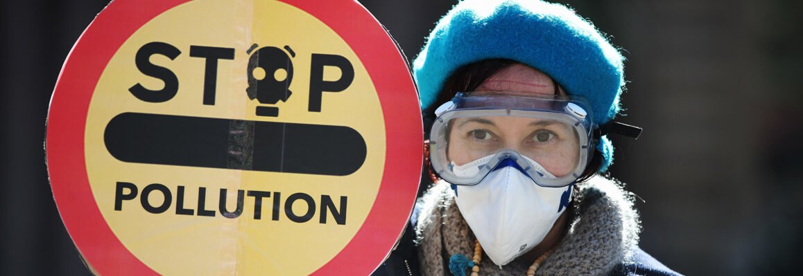 protester holds yellow and red protest sign that reads stop pollution