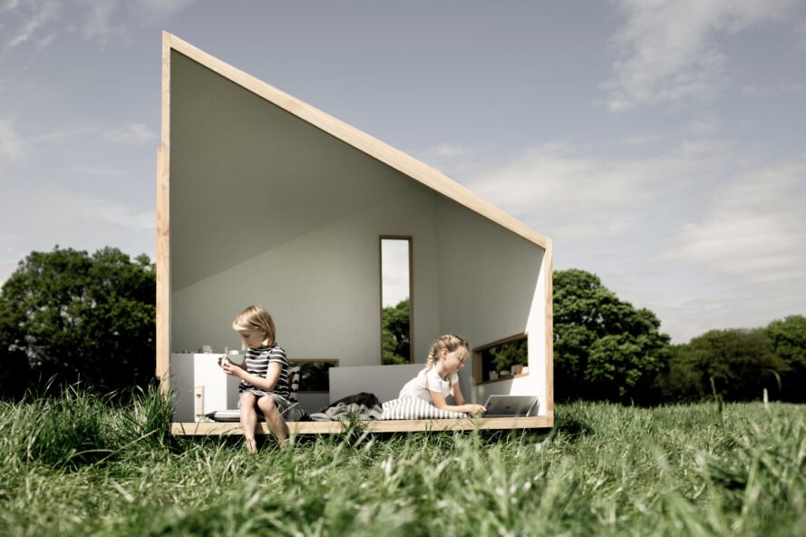 kids sitting inside small wood cabin