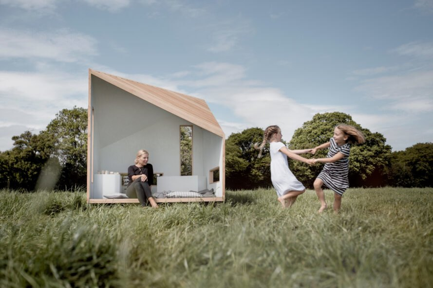 kids running in field outside small cabin playhouse