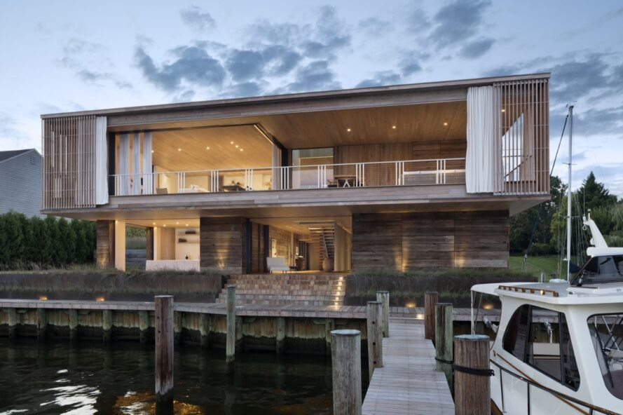 two story home is illuminated by interior lights with a dock beside it
