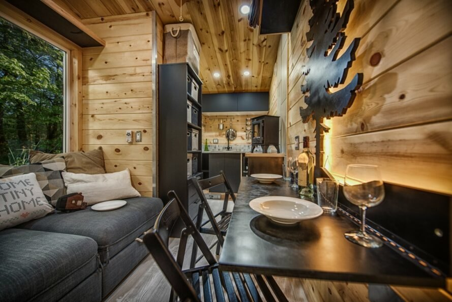wooden-clad interior of tiny home with gray sofa and black fold-up dining table