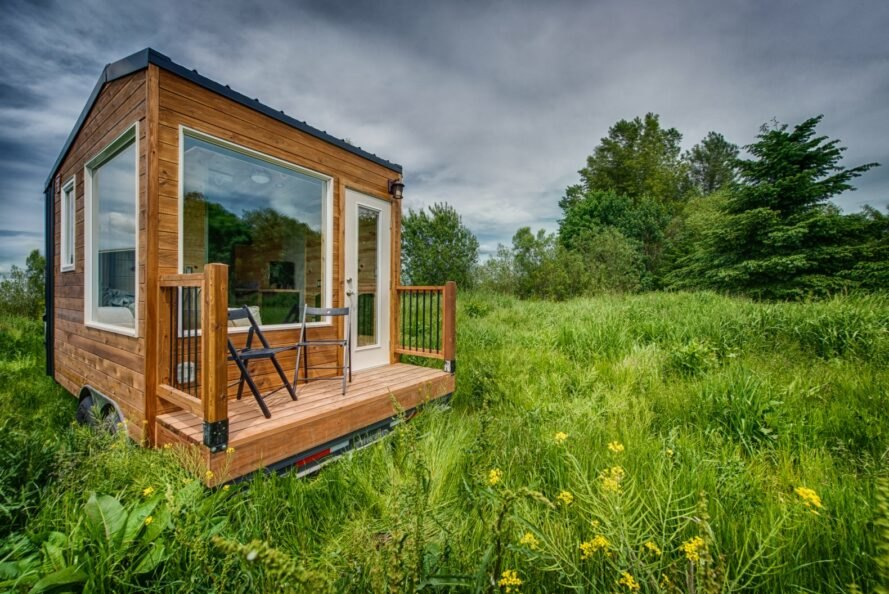 tiny wooden home with large window and front deck