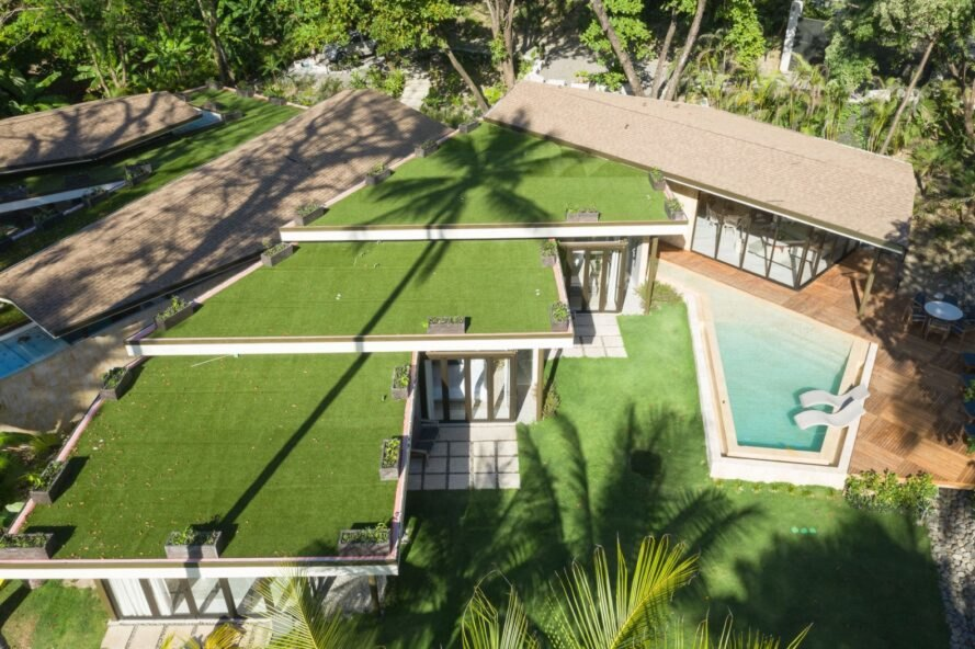 aerial view of home with green roof and a pool