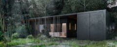 black horizontal cabin surrounded by forest