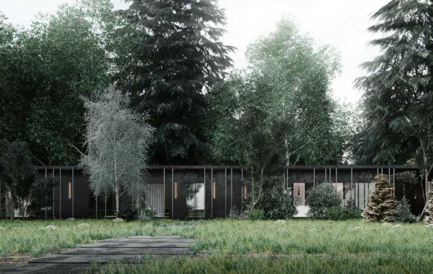 low, elongated black cabin in a forest