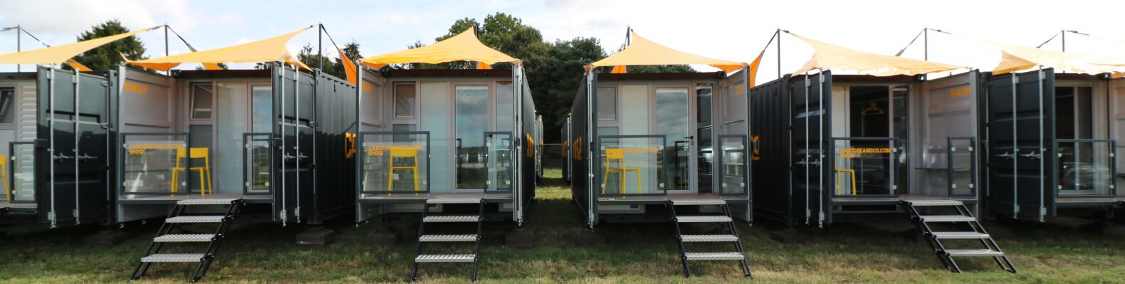 shipping container lodging with pitched yellow roof