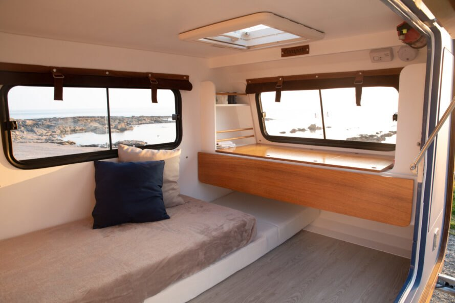 interior of a tiny travel trailer with small bed and desk