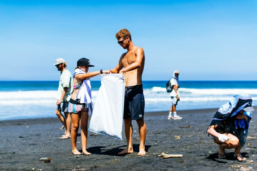 surfers and volunteers take part in a beach cleanup