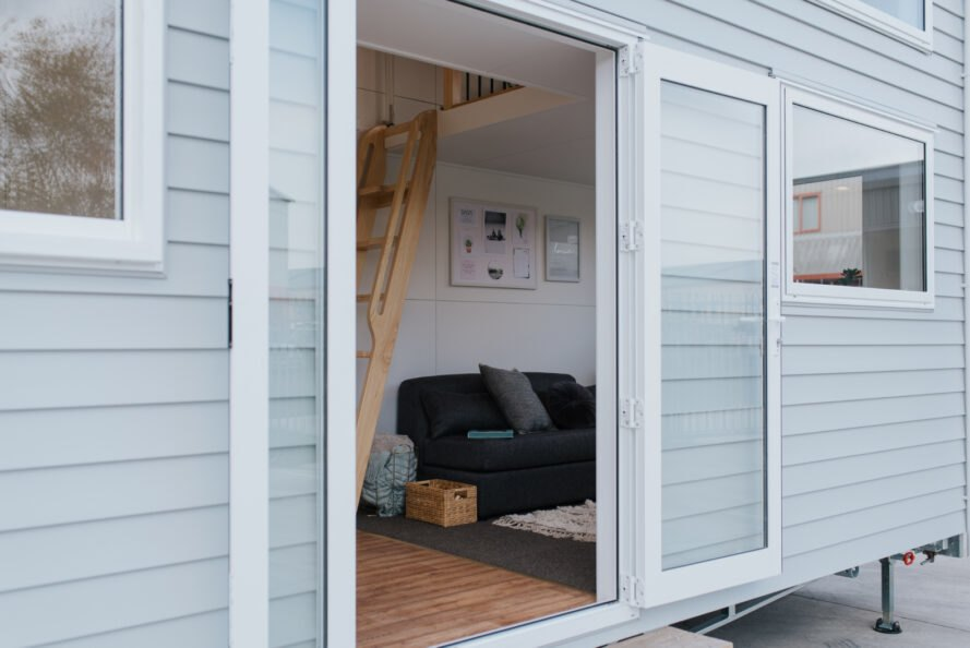 glass doors opening to gray tiny home