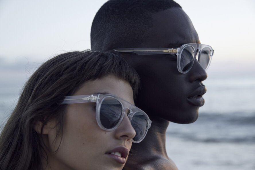 models wear clear framed sunglasses at the beach
