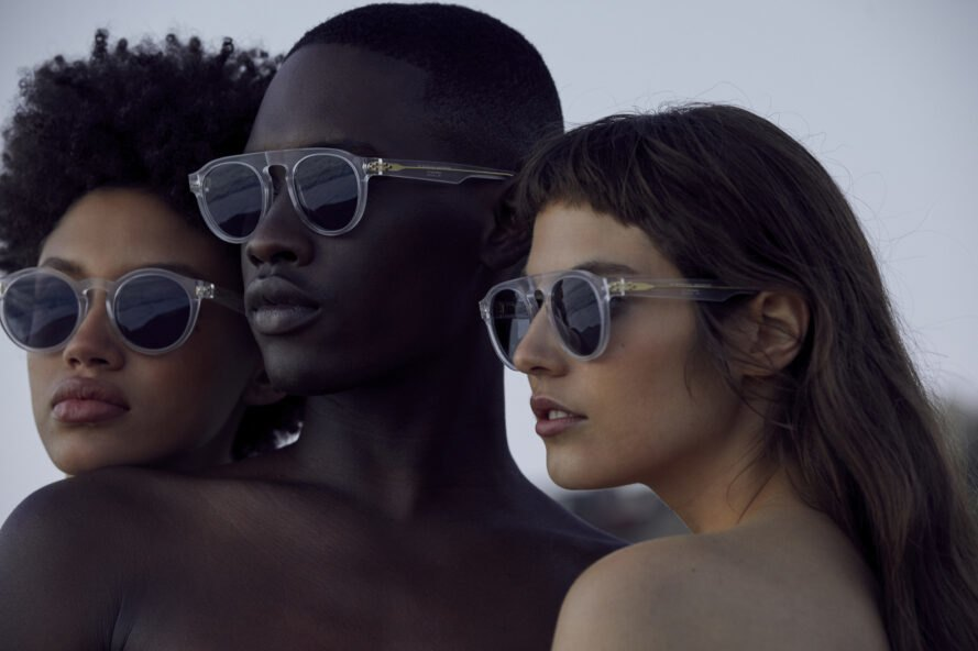 three models wear just humans sunglasses while near the ocean