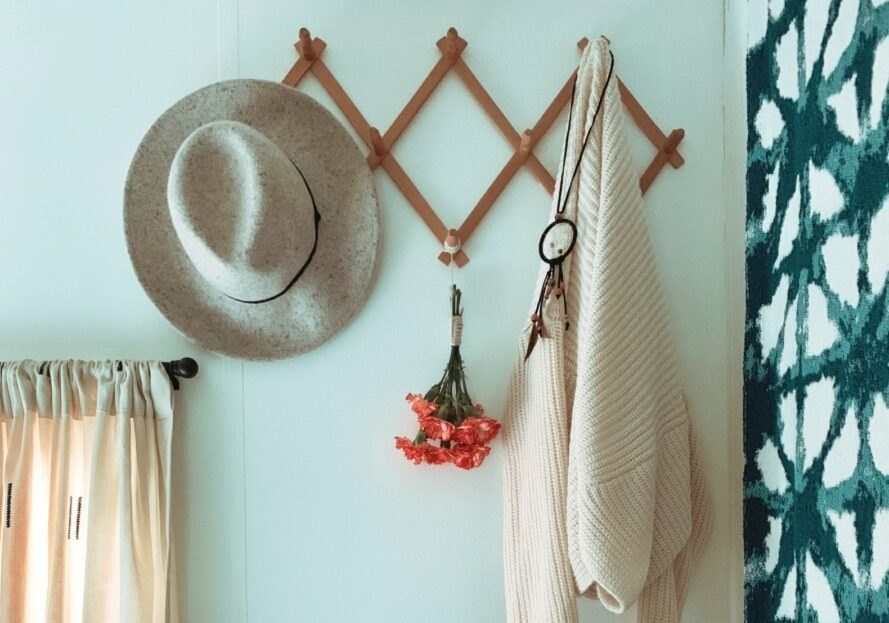 a wall rack with a hat and sweater hanging on it