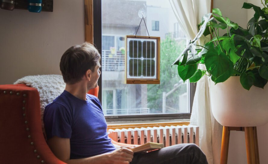 man sitting next to window with framed solar panels