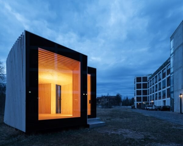 small timber prototype house illuminated with bright interior lights and ceiling to floor glass window