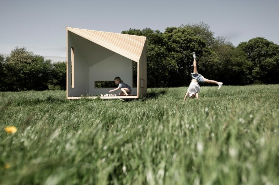 kids playing in a geometric wood cabin