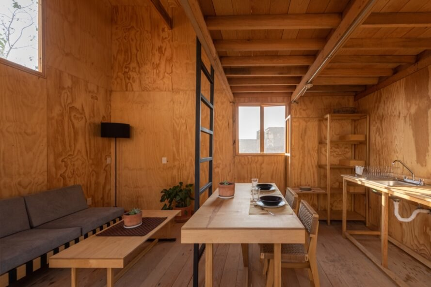 timber-lined room with small sofa, wood dining table and kitchen sink on timber table