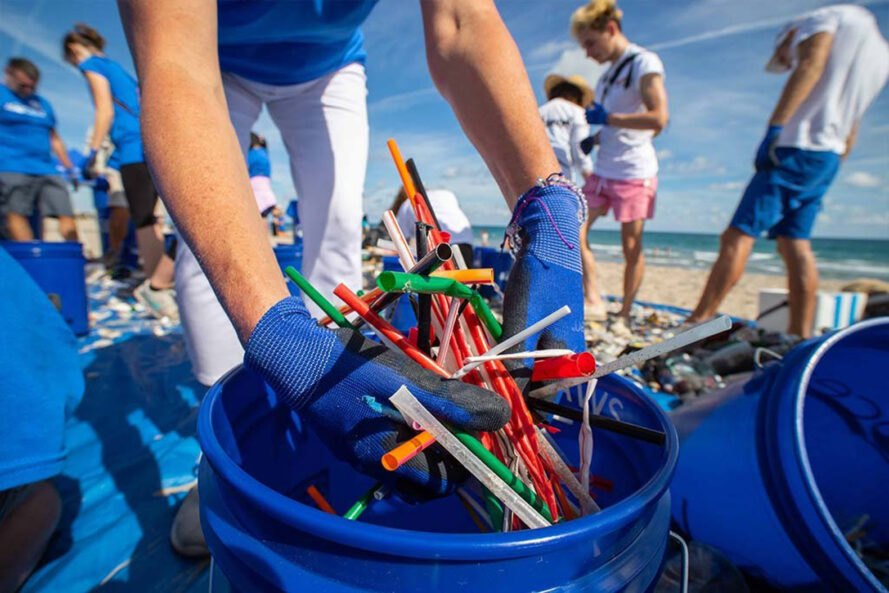 person wearing blue gloves placing waste inside blue bucket at the beach