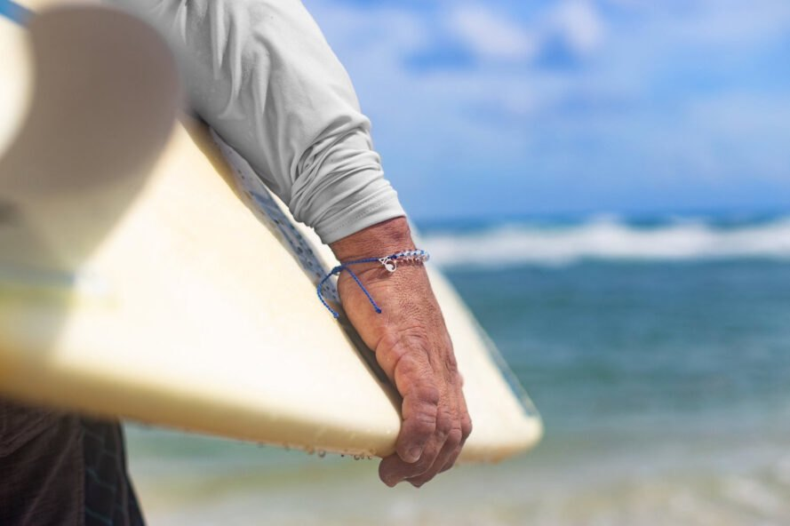 hand of surfer holding surfboard and wearing bracelet