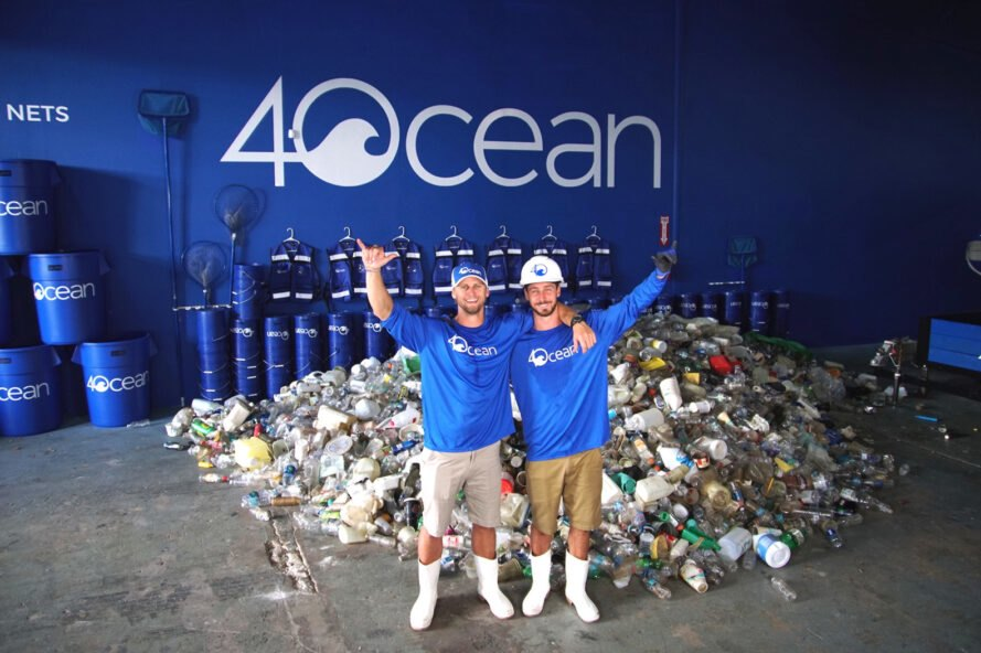 two men wearing hardhats and boots stand in front of pile of plastic waste