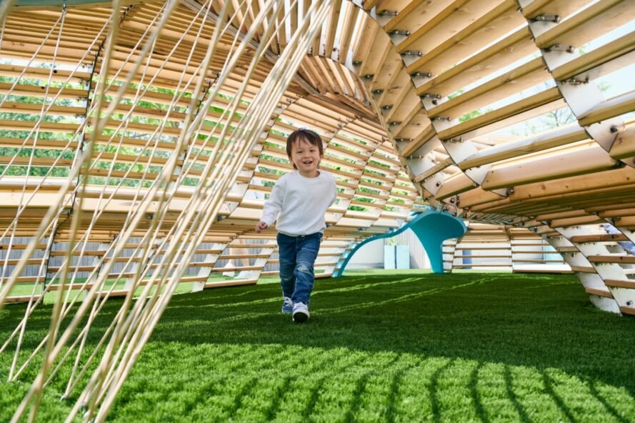 child playing under wood structure