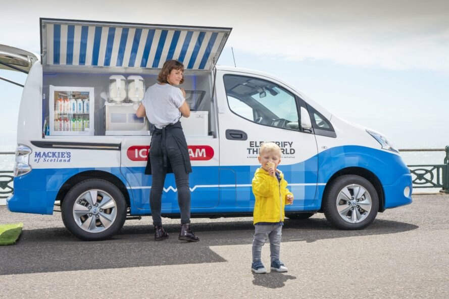 child eating ice cream next to white ice cream van