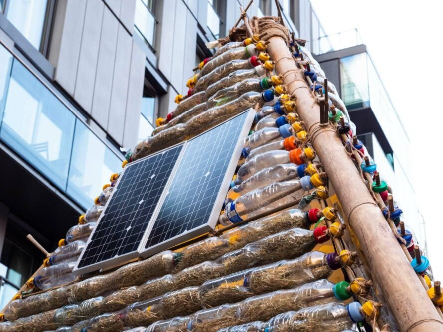 solar panels on outside of shelter made from plastic bottles